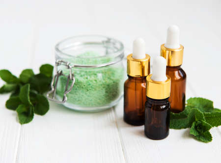 essential aroma oil with massage salt and mint on a white wooden table