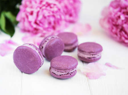 Pink peony with macarons on a white wooden table Stock Photo