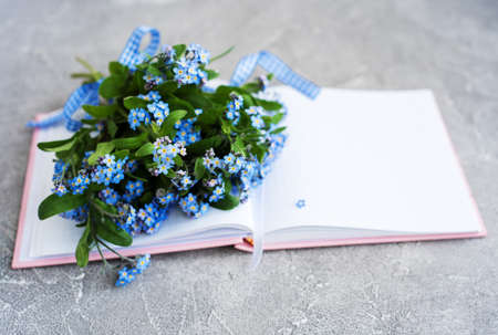 Forget me not flowers and notebook on grey stone background Foto de archivo