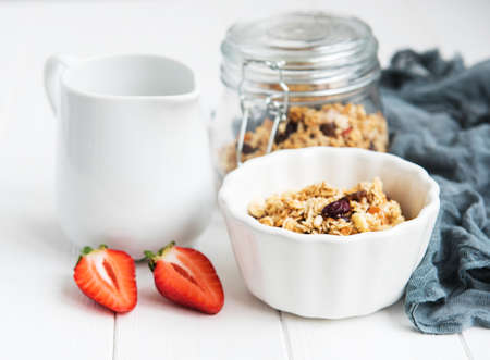 Homemade granola with strawberries on a white wooden table