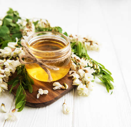Honey with acacia blossoms on a wooden background Imagens