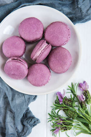 Plate with lavender macarons on a white wooden table