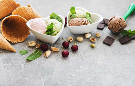 set of ice cream scoops of different colors and flavours with cherries, chocolate and pistachios