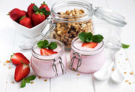 healthy breakfast, yogurt, fresh strawberries and granola on a white wooden table Archivio Fotografico