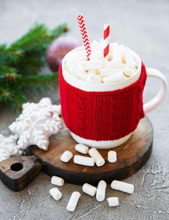 hot chocolate with marshmallows and gingerbread cookie on a old wooden table