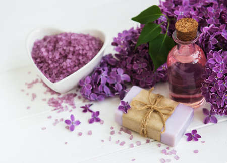 Essential oil with lilac flowers on a old wooden background