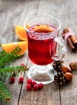 Glass of hot mulled wine with oranges and spices 写真素材