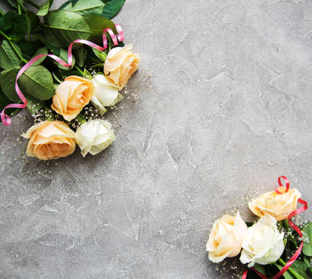 Yellow and white roses on a grey stone background