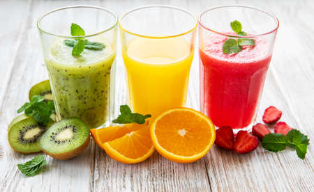 Healthy fruit smoothies and fresh fruits on a old wooden table Standard-Bild
