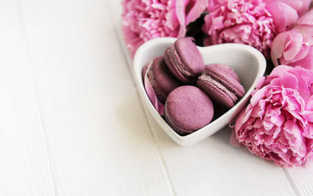 Pink peony flowers with macarons on a white wooden table 免版税图像