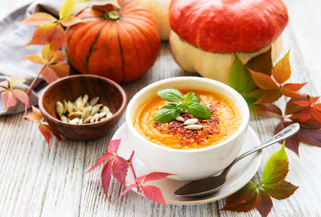 Bowl of pumpkin soup on rustic wooden
