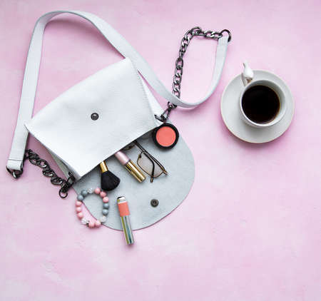 White leather bag with cosmetics on a pink  concrete  background