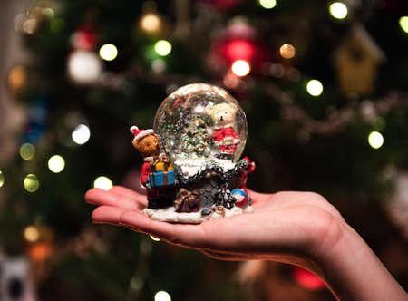 snow glass ball in the hands of the girl opposite bokeh
