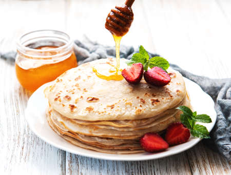 Delicious pancakes with strawberry on white wooden background