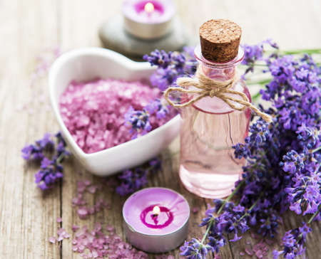 Heart-shaped bowl with sea salt, oil and fresh lavender flowers on a old wooden background