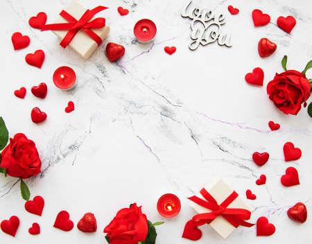 Valentinstag romantischer Hintergrund - dekorative Herzen und Rosen auf Marmorhintergrund