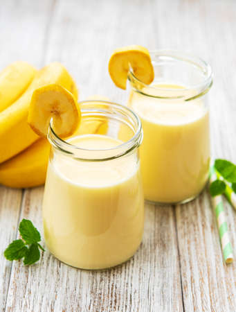 banana yogurt and fresh bananas on a wooden background 写真素材
