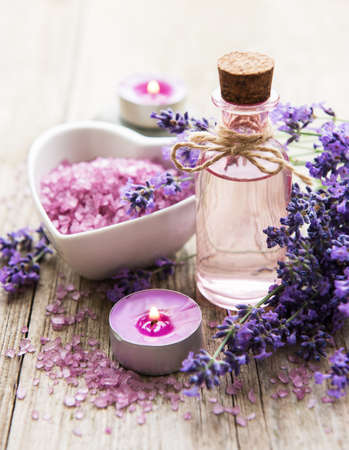 Heart-shaped bowl with sea salt, oil and fresh lavender flowers on an old wooden background