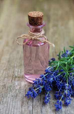 Essential oil with fresh lavender on a  old wooden background Imagens