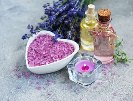 Heart-shaped bowl with sea salt, essential oils and fresh lavender flowers on a stone  background Stock Photo