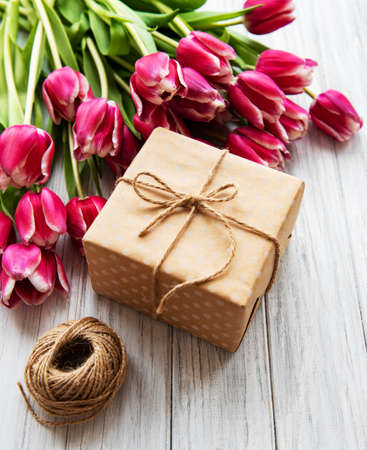 Gift box and tulips bouquet on a old wooden background