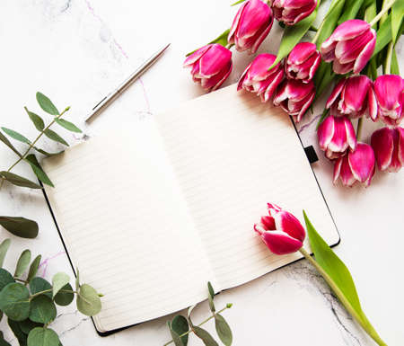 Pink spring tulips and notebook on a marble background