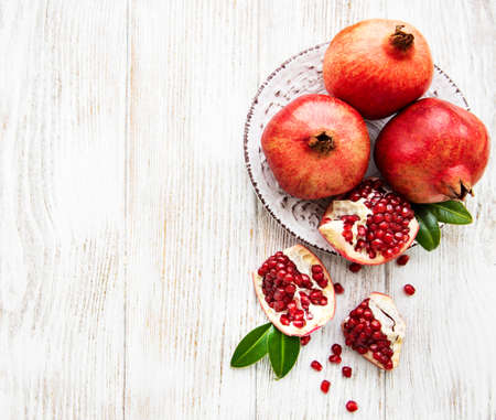 Juicy and ripe pomegranates in the plate  on old wooden table Imagens