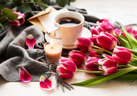 Cup of coffee and pink tulips on a old wooden table 스톡 콘텐츠