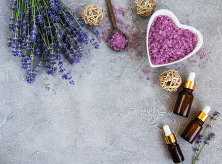 Heart-shaped bowl with sea salt and fresh lavender flowers on a concrete background Stock Photo