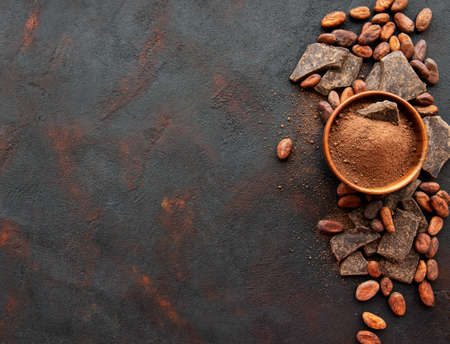 Natural cocoa powder and cocoa beans on a black background