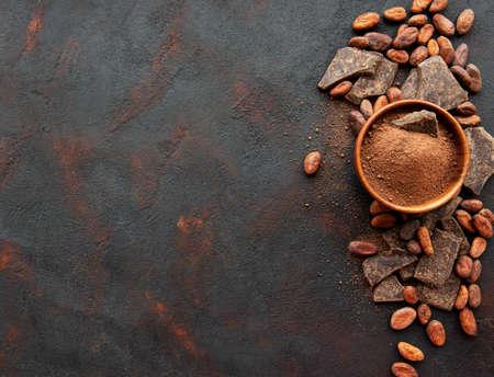 Naturalny proszek kakaowy i ziarna kakaowe na czarnym tle Zdjęcie Seryjne