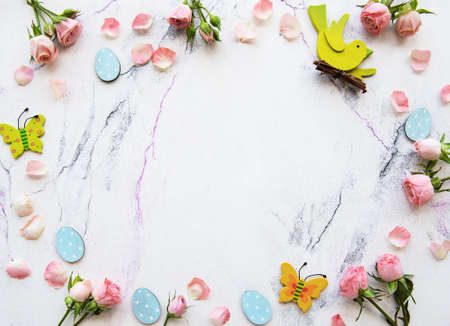 Spring holiday theme, pink roses and decorations on a white marble background