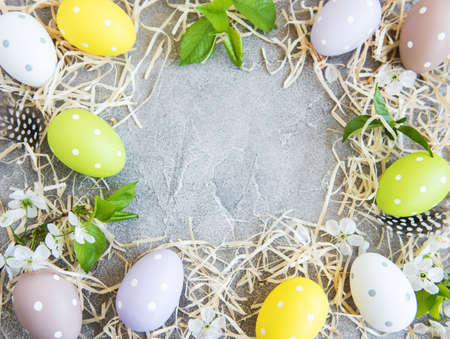 Easter eggs, straw and spring blossom on a concrete background Stock Photo