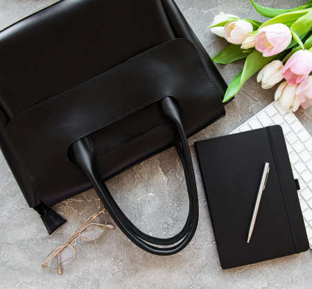 Black leather bag and flowers on a grey concrete background