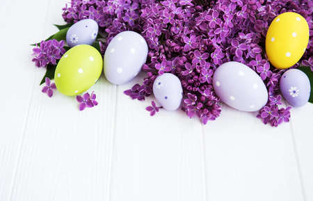 Easter eggs and spring lilac flowers on a white wooden table 写真素材