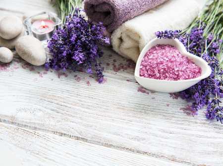 Heart-shaped bowl with sea salt, soap and fresh lavender flowers on a wooden background