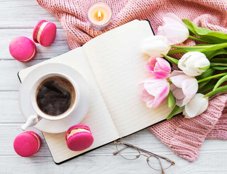 Blogger or freelancer workspace with coffee, tulips, macaroons and notebook