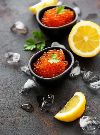 Red caviar in bowls on a old black background
