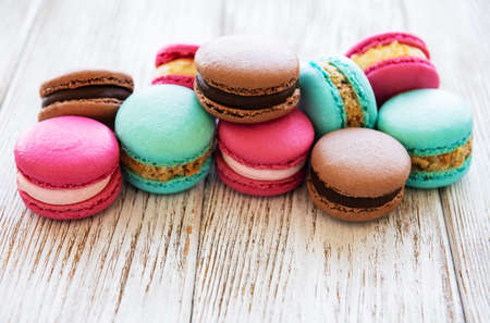 Colorful macaroons and tulips on a white wooden  background 免版税图像