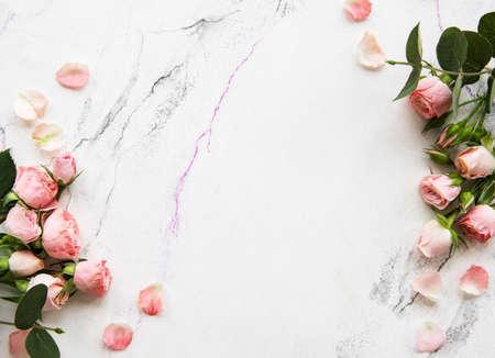 Fondo de vacaciones con rosas rosadas sobre un mármol blanco