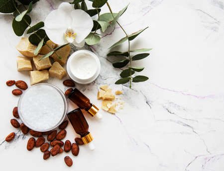 Natural spa ingredients with cocoa beans, cocoa butter and orchid flowers on a white marble background