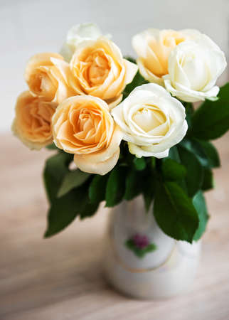 Yellow and white roses in a vase on a table Archivio Fotografico
