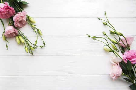 Fresh pink eustoma flowers frame on wooden background