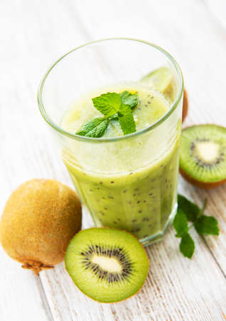 Glass of kiwi smoothie with fresh fruits on a white wooden table