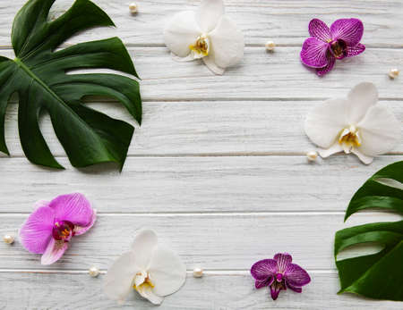 Tropical leaves monstera and orchid flowers on a white wooden  background