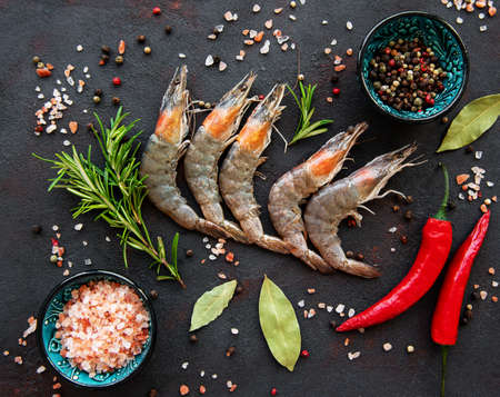 Fresh raw  prawns and spices on  black stone background