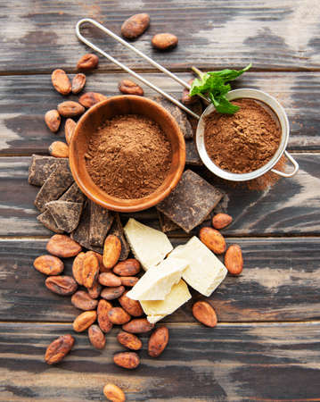 Natural  cocoa powder, cocoa butter and cocoa beans  on a wooden background Reklamní fotografie - 122416518