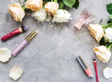 Roses and cosmetic - flat lay on a stone background