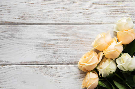 Yellow and white roses on a old wooden table Imagens