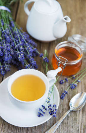 Cup of tea and honey with lavender flowers on a old wooden table